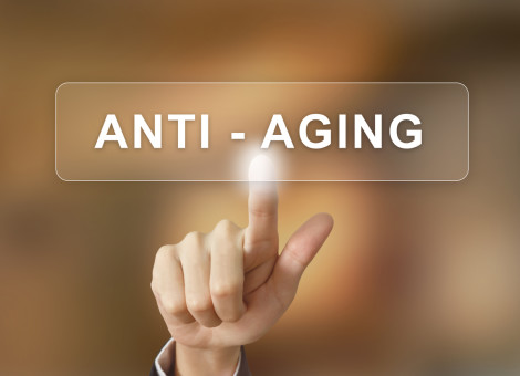 business hand pushing anti aging button on blurred background
